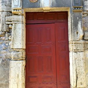 Porte en bois grenat dans son écrin de pierre © Greta Garbure